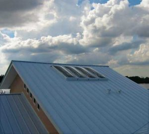 tandem row of maxim skylights on a sloped metial roof under a stormy sky